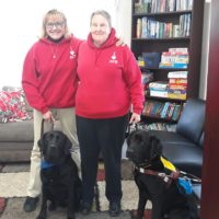 Therapy Dog Clive and Guide Dog Nate are sitting in front of Cheryl and Nancy who are wearing red ACB hoodies.
